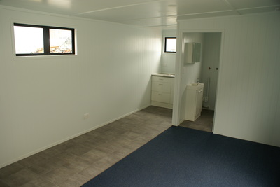 Interior of portable cabin showing bathroom and living area
