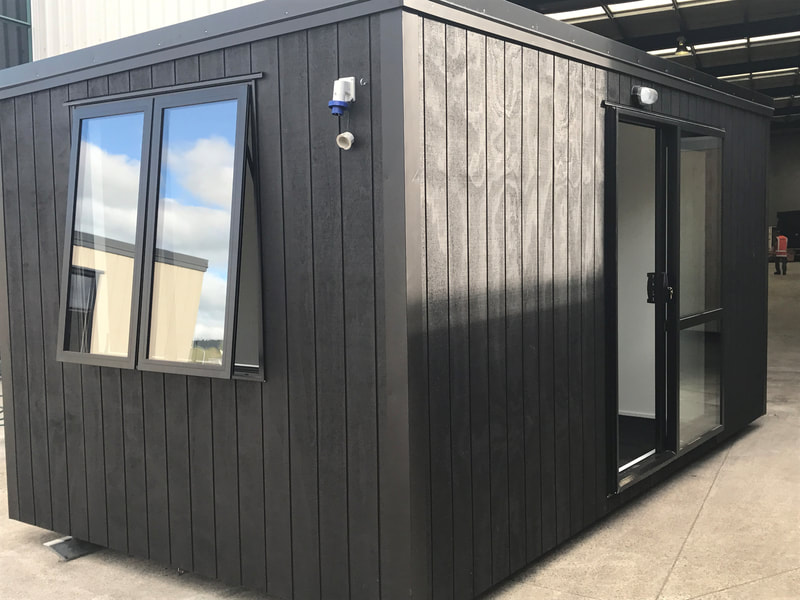 Small, black portable building in factory