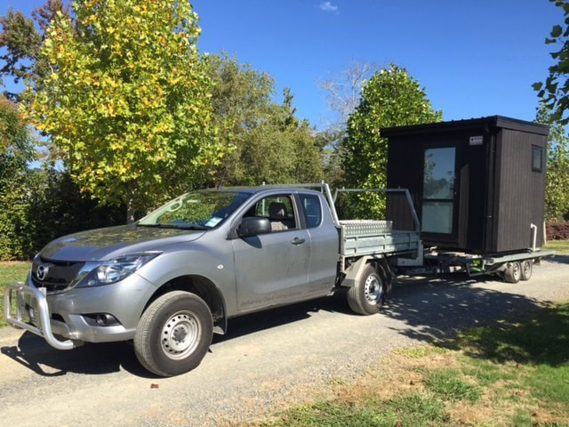 Small black portable building on trailer